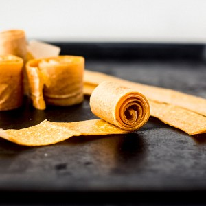 roll of mango fruit leather coiled on a black sheet