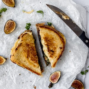 vegan honey grilled cheese sliced on a white table next to figs