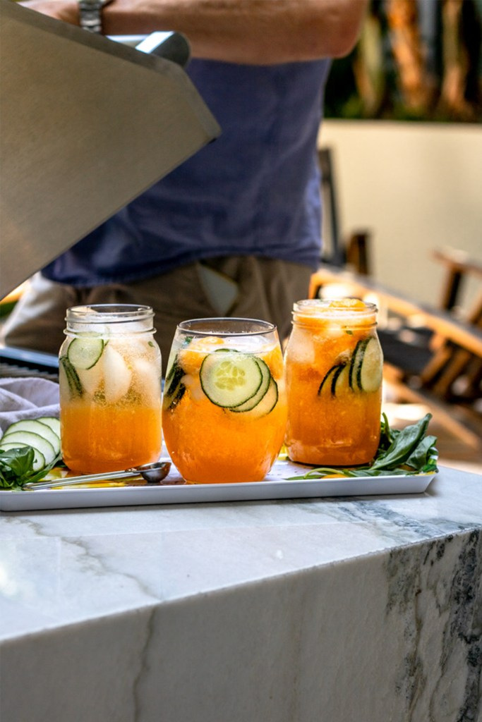 tray of three cucumber melon gin fizz cocktails on a marble table next to a person opening a grill for a BBQ