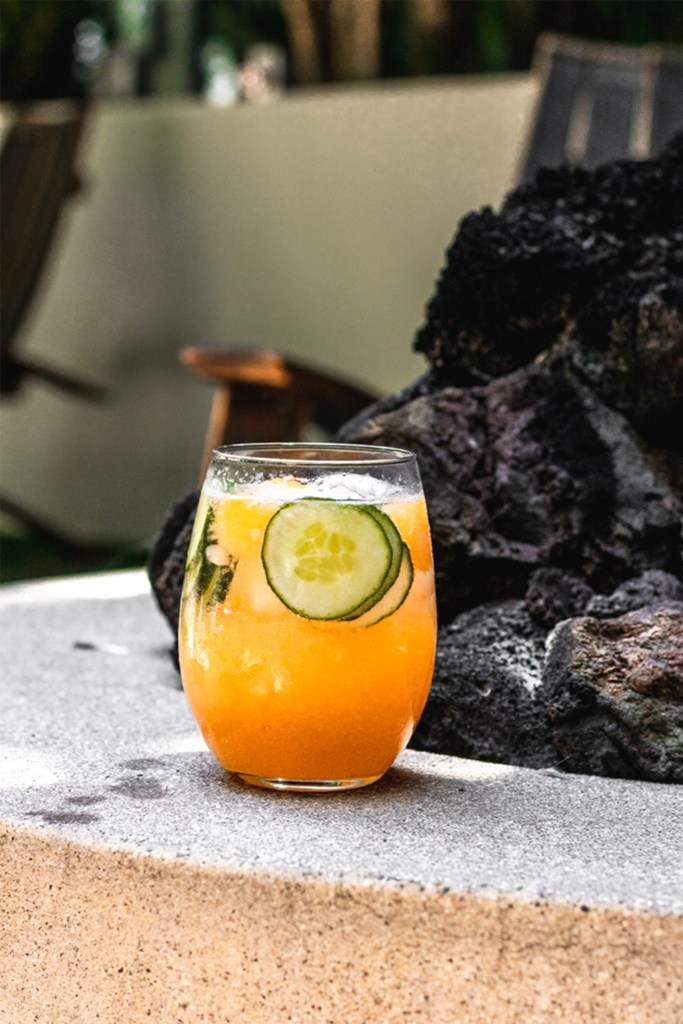 one cantaloupe cocktail next to a fire pit