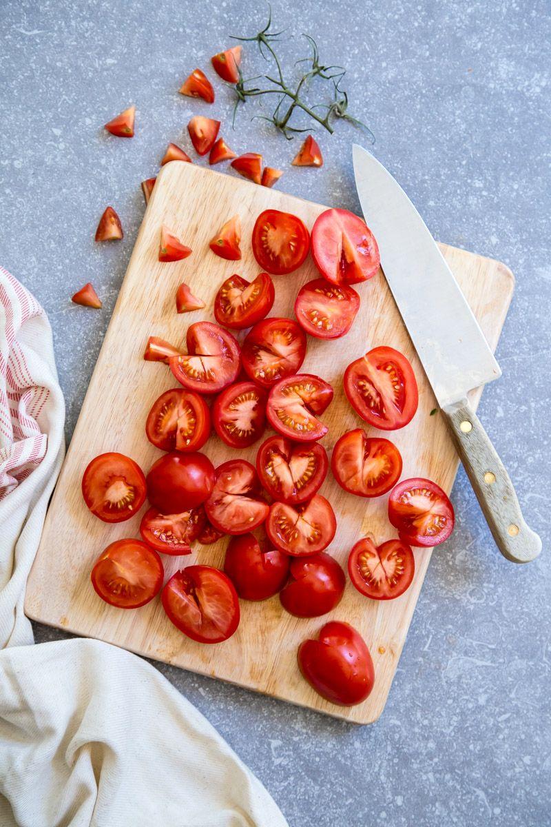 Carota e dimezza, pomodori freschi su un tagliere.