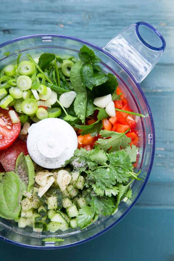 Raw vegetables and herbs in a food processor