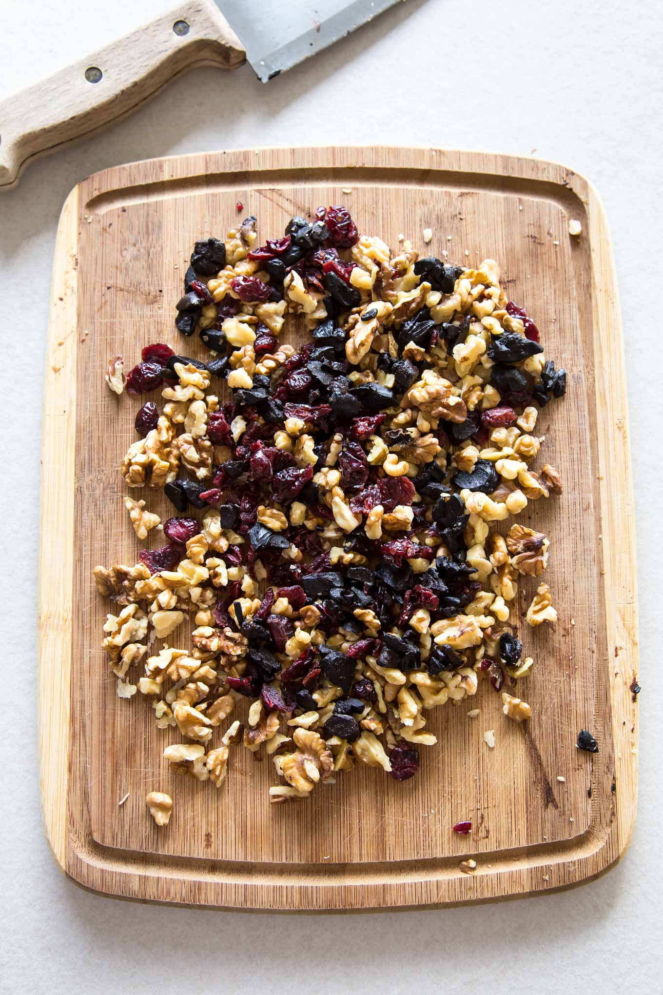 Chopped cranberries, nuts and black garlic spread on a chopping board