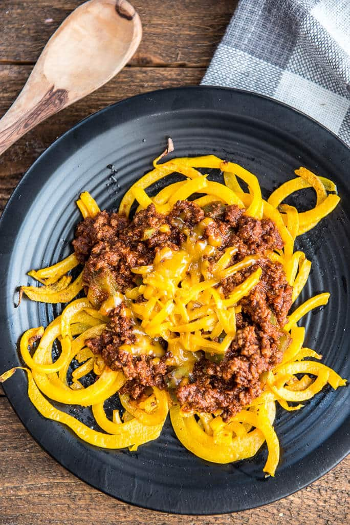 Overhead shot of Easy Skillet Cincinnati 'Skyline' Chili with Butternut Squash Noodles on a black plate with a white and gray checked napkin