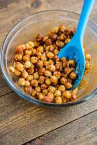 Chickpeas tossed with seasonings in bowl getting ready to bake for Crispy Chickpea Tostadas