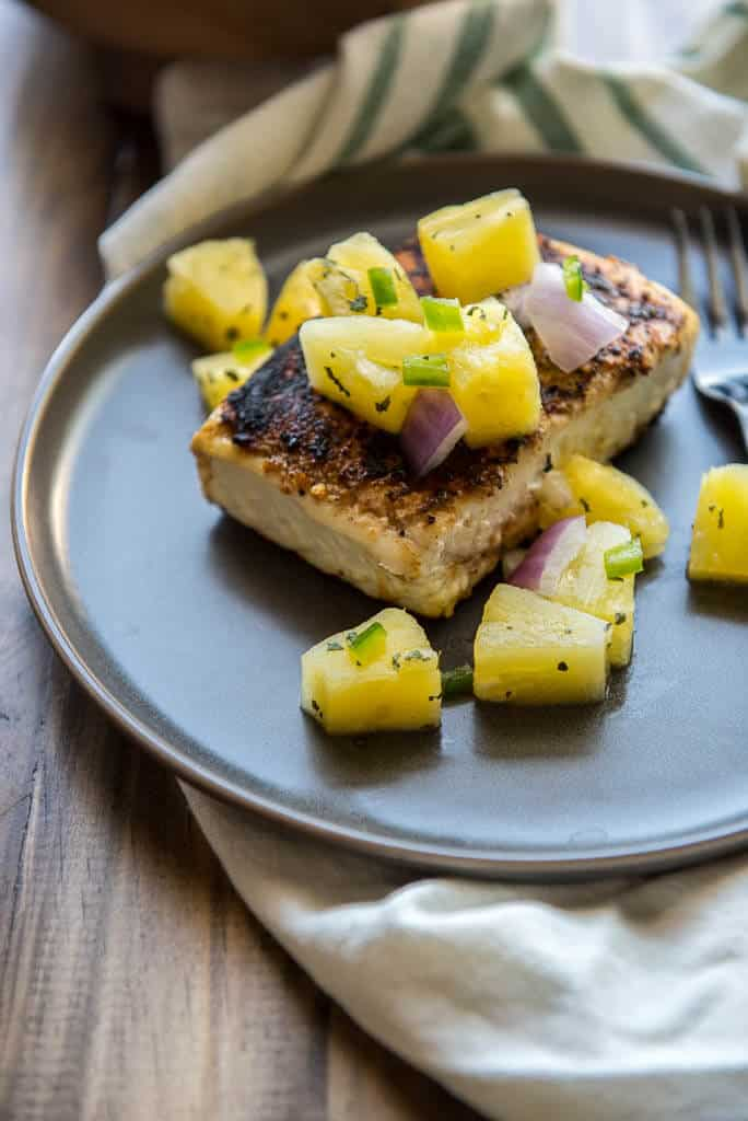 Pan Seared Halibut Recipe with Pineapple Salsa on gray plate with white and green napkin on wood table.