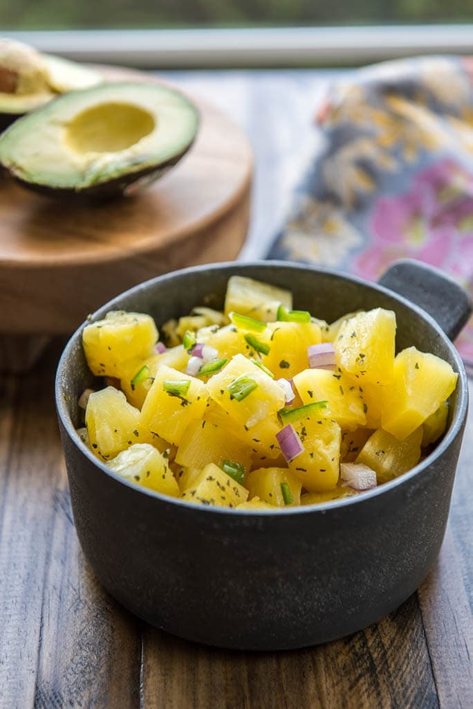 Fresh pineapple salsa in a metal bowl in front of avocado and a floral napkin for Shrimp Tacos in a Bowl with Pineapple Salsa.