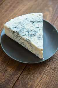 A wedge of gorgonzola cheese and a gray plate.