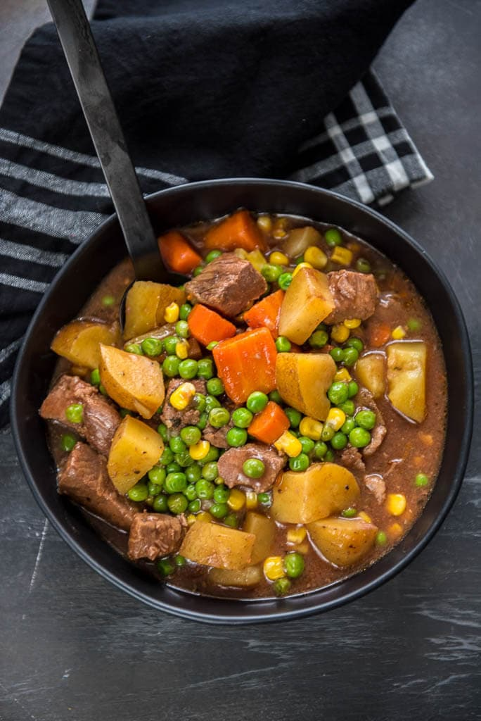 Slow Cooker Beef Stew in Black Bowl from overhead on gray table with black napkin
