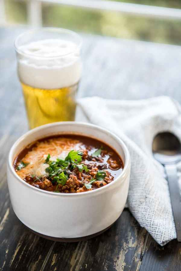 The Best IPA Beer Chili in a white bowl served with a frothy beer in a glass