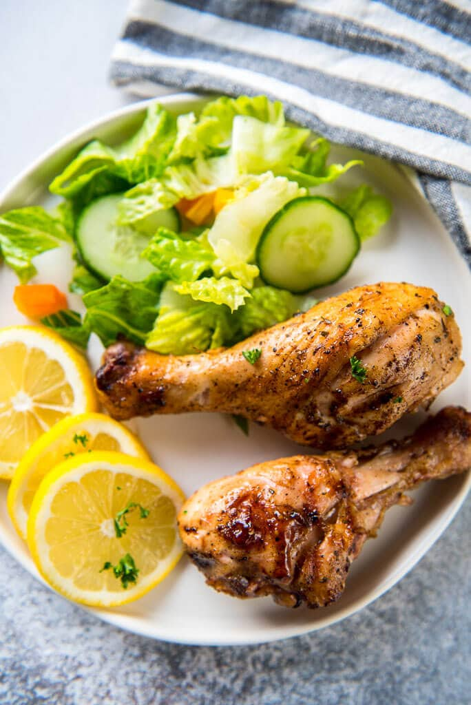 two Lemon Herb Grilled Chicken Drumsticks on a white plate with sliced lemons and a green tossed salad