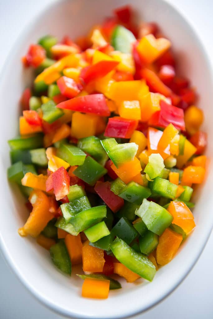 red, yellow, orange and green peppers chopped in white bowl ready to make stuffed pepper soup