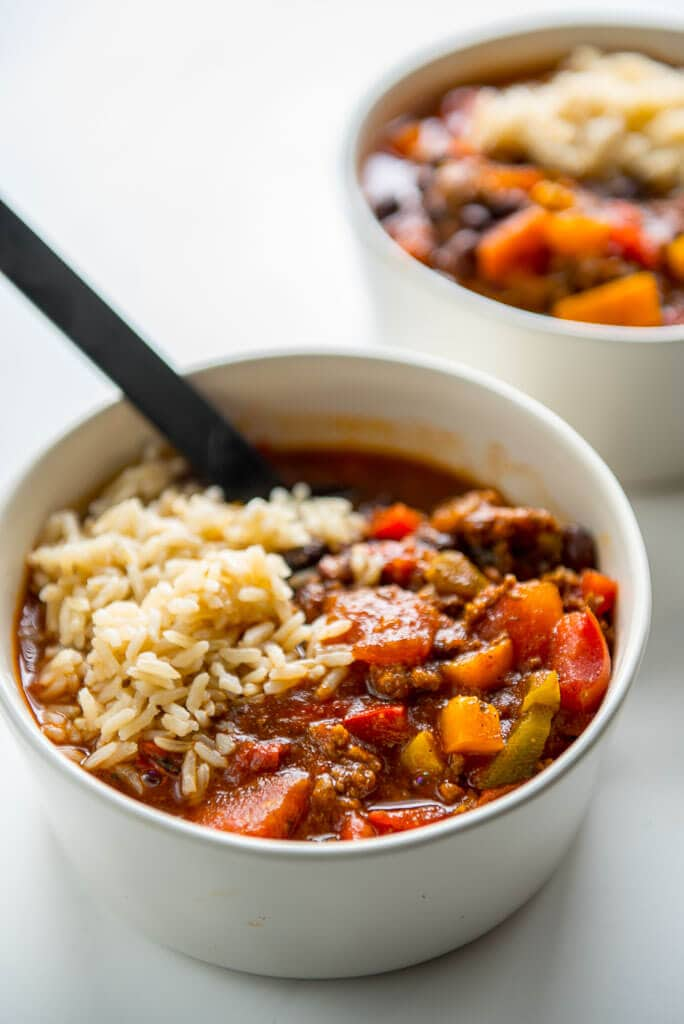 stuffed pepper soup in white bowl topped with brown rice