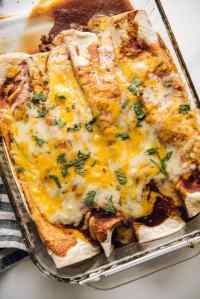 Easy Beef Enchiladas topped with melted cheese in glass casserole dish