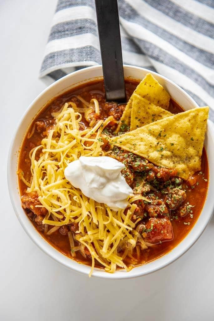 white bowl full of healthy chili topped with chips, cheese and sour cream