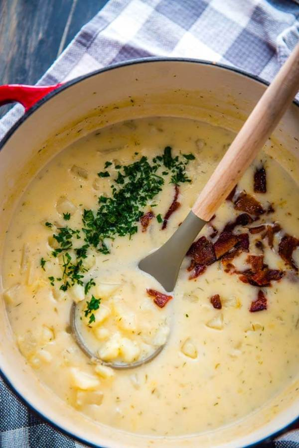 creamy potato soup in a red and white cast iron pot topped with bacon and parsely