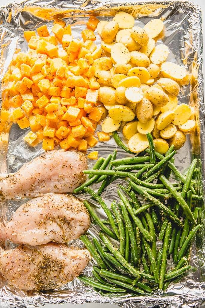 chicken, green beans, potatoes and butternut squash on a sheet pan ready to cook