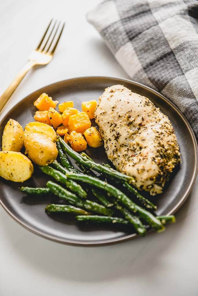 chicken breast with green beans potatoes and butternut squash on a gray plate with a gold fork
