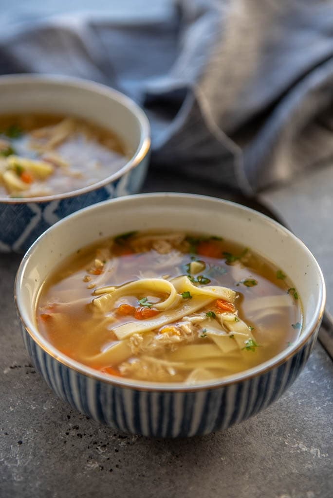 chicken noodles soup in blue and white bowl
