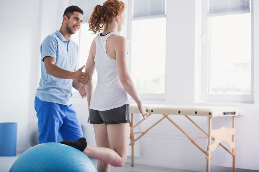 Physiotherapist supporting woman during rehabilitation with ball