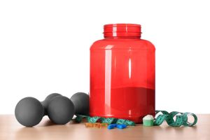 Protein powder, pills, dumbbells and measuring tape on table