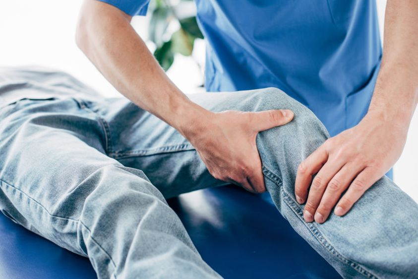cropped view of chiropractor massaging leg of patient