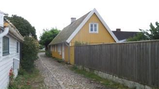Gelbes Holzhaus in einer Straße aus Kopfsteinpflaster
