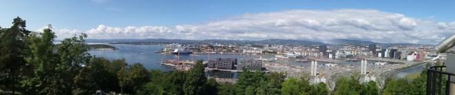 Blick auf Oslo mit dem Meer auf linker Seite, Krezfahrtschiff und dicht besiedelter Stadt auf rechter Seite.
