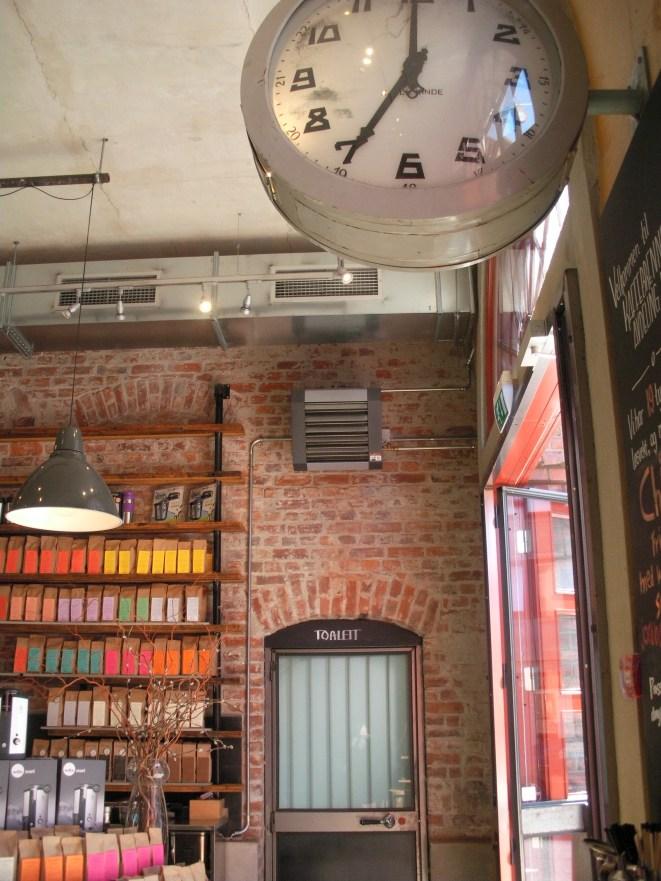 Alte rotes Backsteine, davor Regale mit Kaffee und einer alten Bahnhofsuhr im Vordergrund an der rechten Wand.