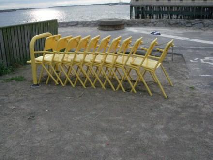 Gelbe Stühle, die man sich wie bei einem Einkaufswagen gegen Geldpfand aus einem Gestell nehmen kann