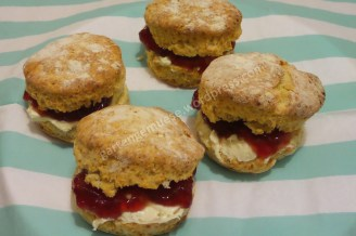 Vier runde Brötchen gefüllt mit roter Marmelade und einer weißen Creme auf einer türkis gestreiften Serviette