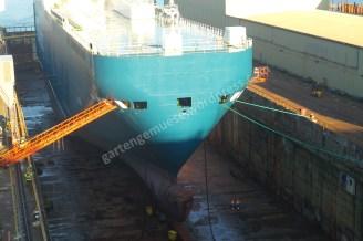 Großes Schiff in einer Werft. Davor sind ganz klein zwei Menschen zu erkennen