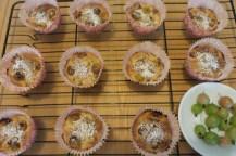 In pinken Papierförmchen stecken Muffins mit deutlich hervorstehenden Stachelbeeren und Puderzucker dekoriert. Vorne rechts liegen Stachelbeeren auf einem Teller
