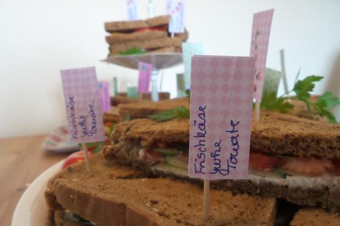 Sandwiches in Nahaufnahme mit kleinen Fähnchen. Auf einem steht: Frischkäse, Gurke, Tomate