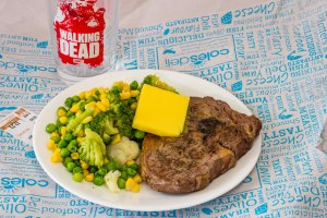 This is a photograph of Scotch fillet steak with vegetables. The meat was oven baked with the MEATER thermometer. There's also a big wedge of butter on the steak and a walking dead glass.