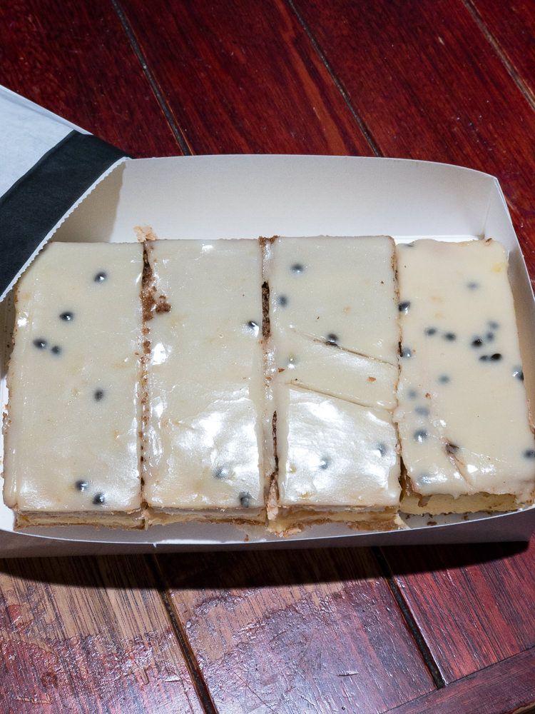 This is a photograph of Vanilla slice from Dobinsons Bakery Cafe. I shot the photograph at Westfield Belconnen. It shows a tray of four slices in a cardboard box.