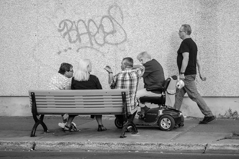 A city bench and some people chatting