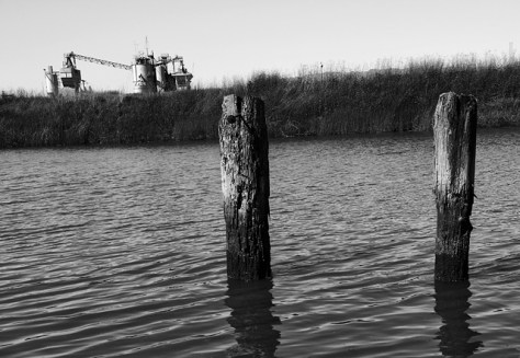 Old pilings and river side industrial plant