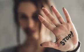 Mujer con la palabra Stop escrita en la palma de la mano en referencia a Stop agresiones machistas
