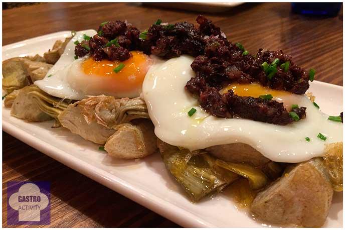 Huevos rotos sobre alcachofas y butifarra negra El Patio del Fisgón Chamberí Madrid