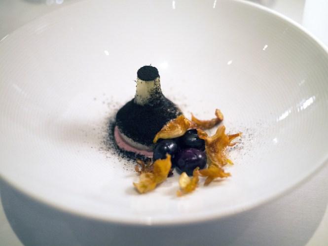 Artistok med fermenterede blåbær og flager af artiskokblade.