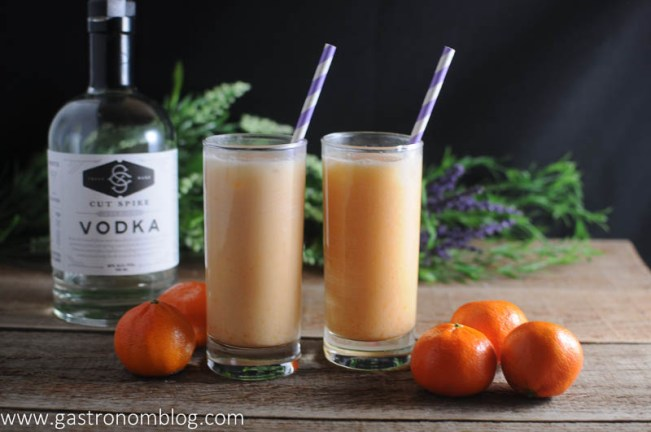 Dreamsicle cocktail in two highball glasses with clementines and vodka in background