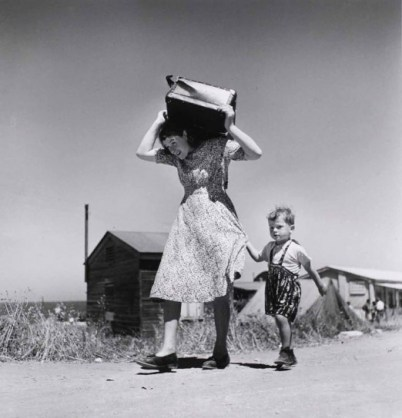 robert-capa-woman-carrying-luggage-accompanied-by-a-small-boy