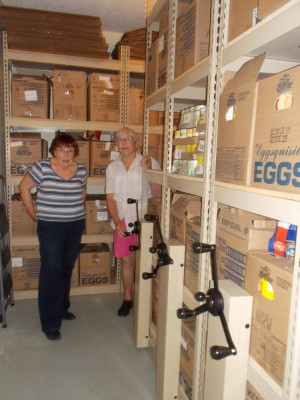 Sharon Herriman and Ida Wegelin stand next to our new sliding shelving system.