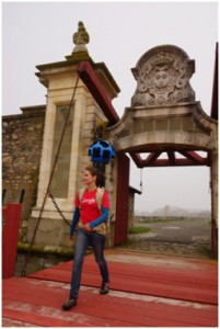One of Google's Street View operators passes through the Dauphin Gate at the Fortress of Louisbourg while collecting imagery with the Trekker Street View backpack. © Parks Canada
