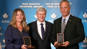 Prime Minister Stephen Harper presents Aaron Semkuley and Mylaine Tsaprailis, accepting on behalf of Dr. Myron Semkuley and Elaine Semkuley, with the Prime Minister's Volunteer Award for Lifelong Achievement during a special ceremony in Toronto marking the third Prime Minister's Volunteer Awards.