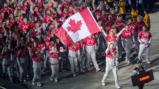 Mark Oldershaw waves the Canadian flag as Team Canada enters the stadium at the Rogers Centre during the opening ceremony of the 2015 Pan American Games.
