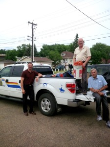 RCMP, Sport Central and Alberta's Promise help load up an RCMP truck with sports equipment for kids. (L-R) Nathan Cross, Alberta's Promise; Sheldon Oleksyn, Sport Central; Wilf Brooks, Premier's Council on Alberta's Promise.