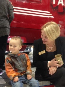 STARS President and CEO Andrea Robertson with a young visitor at the STARS Open House in Calgary. STARS' helicopter BK117 is in the background