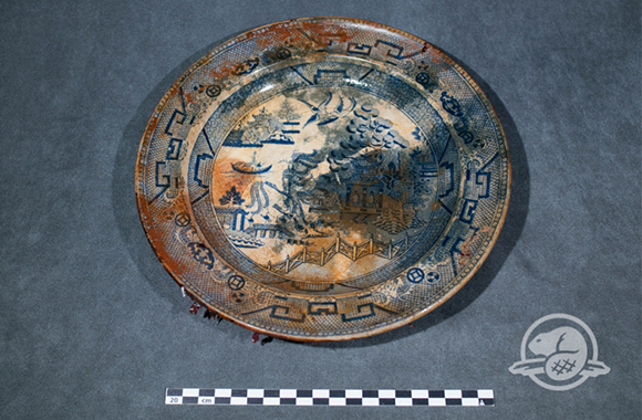 "Fine earthenware, blue willow pattern, ""Royal Patent Staffordshire China"" (ca. 1820-1845) This fine earthenware plate is decorated with the blue willow pattern, the most common transfer print used on ceramic tableware in Europe and North America during the 19th century. Finding plates was not a complete surprise to the underwater archaeologists since ceramic tablewares were commonly used aboard Royal Navy ships. Interestingly, in 1879, an Inuk by the name of Puhtoorak reported to members of the Schwatka search expedition that he had boarded a ship trapped in ice off the Adelaide Peninsula, now identified as HMS Erebus. He recalled seeing the deserted ship in ""complete order"", finding many ""spoons, knives, forks, tin plates, and china plates""."